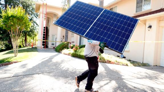 A Sunrun employee carries a solar panel to an installation at a home in California in May.