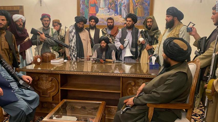 """Taliban fighters sit inside the presidential palace in Kabul on August 15. The palace was <a href=""""https://www.cnn.com/2021/08/15/politics/biden-administration-taliban-kabul-afghanistan/index.html"""" target=""""_blank"""">handed over to the Taliban</a> after being vacated hours earlier by Afghan government officials."""