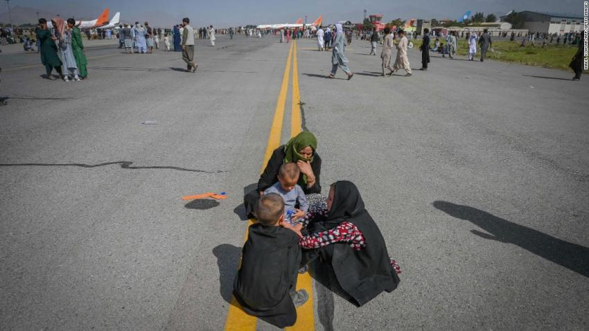 Afghans sit on the tarmac as they wait to leave the airport in Kabul on August 16.