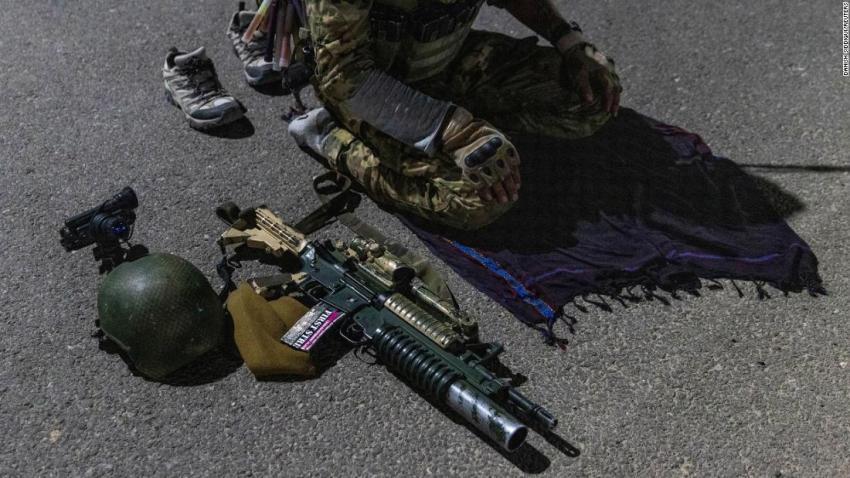 A member of the Afghan Special Forces prays on a highway before a combat mission in Afghanistan's Kandahar province on July 11.
