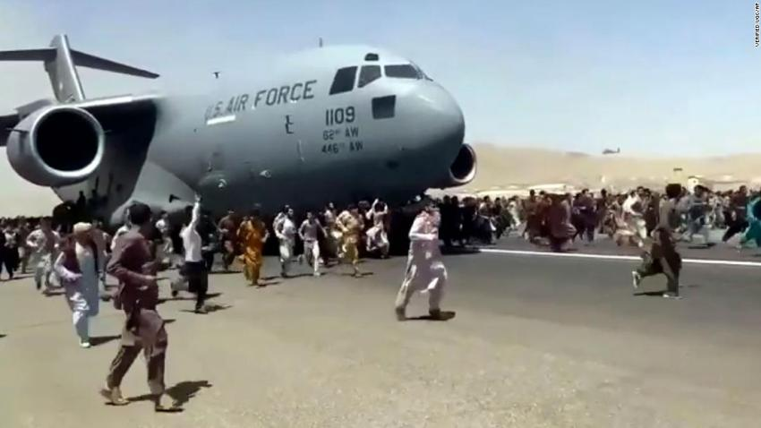 """Afghans run alongside a US Air Force transport plane on the runway of the Kabul airport on August 16. <a href=""""http://cnn.com/videos/world/2021/08/16/kabul-clinging-to-airplane-taking-off-tarmac-afghanistan-ward-vpx.cnn/video/playlists/afghanistan-falls-to-the-taliban/"""" target=""""_blank"""">Video showed</a> people clinging to the fuselage of the aircraft as it taxied."""