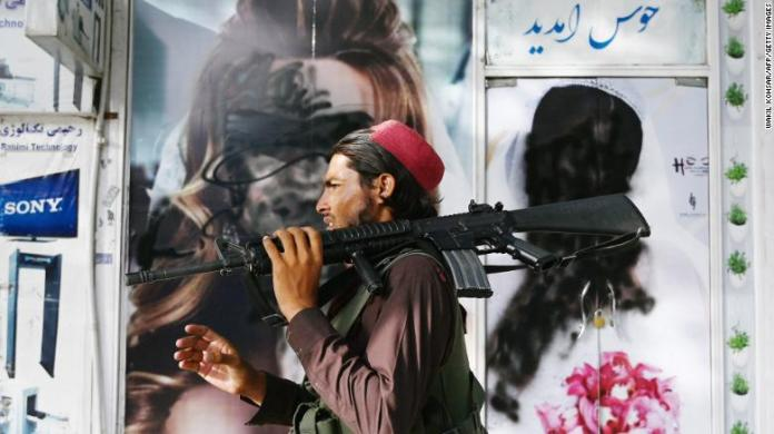 A Taliban fighter walks past a Kabul beauty salon, where images of women are defaced by spray paint.