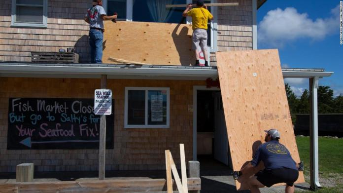 Men work on covering the windows at Salty's Clam Shack as Henri approached Westerly, Rhode Island, on August 21.
