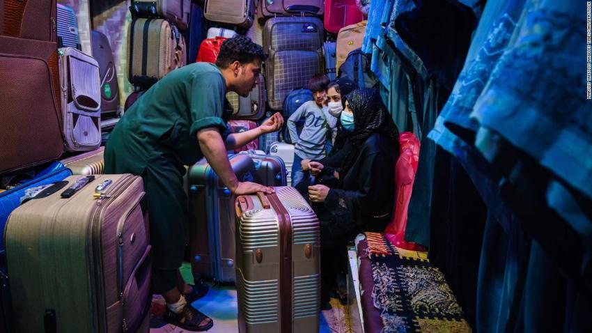 Amir Saib Zada negotiates with customers at his shop that sells luggage and burqas in Kabul's Lycee Maryam Bazaar on August 22.