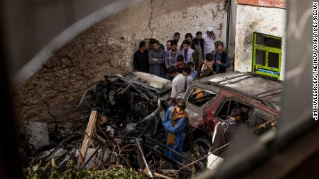 Relatives and neighbors inspect the remains of the US Hellfire missile strike in the residential compound in Kabul.