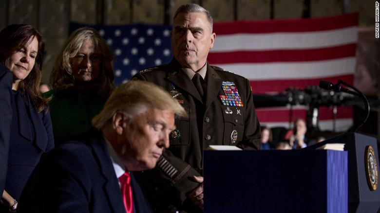 Joint Chiefs Chairman Gen. Mark Milley, top center, watches as President Donald Trump signs the National Defense Authorization Act for Fiscal Year 2020 at Andrews Air Force Base, Maryland, December 2019.