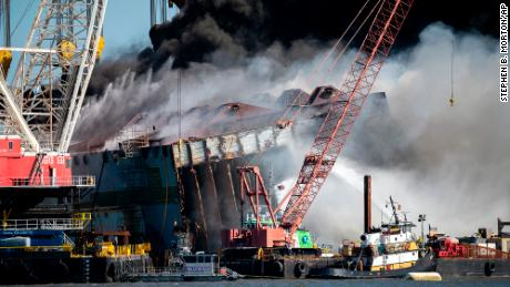 Firefighters spray water into the cut-away mid-section of the Golden Ray on May 14, 2021.
