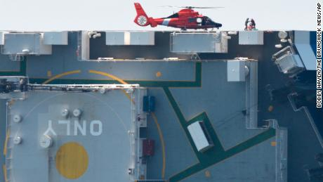 Members of the US Coast Guard unload supplies from a Coast Guard helicopter from the side of the Golden Ray on September 9, 2019, the day after it capsized.