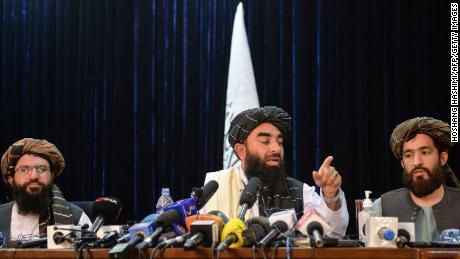 तालिबान के प्रवक्ता जबीहुल्ला मुजाहिद (सी) ने १७ अगस्त को काबुल में अफगानिस्तान के तालिबान के अधिग्रहण के बाद पहले समाचार सम्मेलन को संबोधित करते हुए इशारों में इशारा किया।