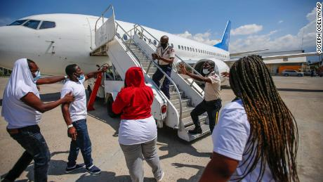 Police officers try to stop an exiled man from boarding the same plane in which he and others were deported.