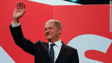 Olaf Scholz waves at the SPD headquarters after the projections are broadcast on TV in Berlin.
