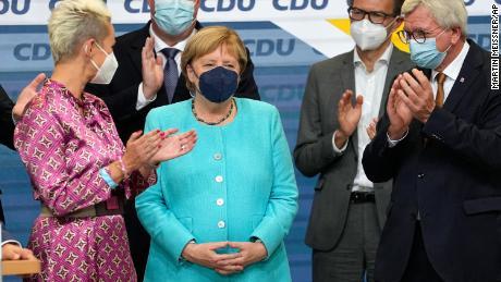 German Chancellor Angela Merkel stands as leading CDU members applaud on Sunday.