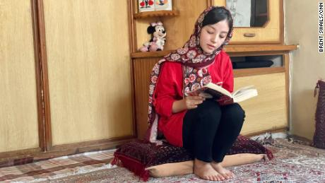Sanam, 16, barred by the Taliban from going to school, continues her studies from home.