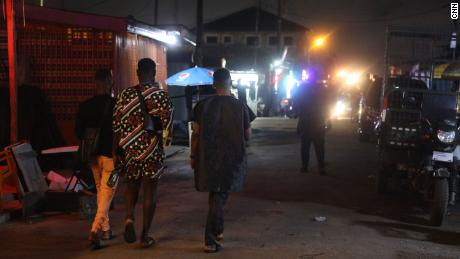 A group of gay men walking on a street in Accra, they met in this neighborhood to attend a wake party for a member of their community.
