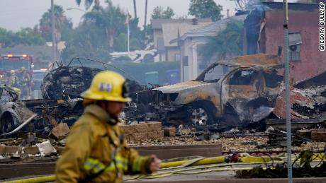 Firefighters searched for charred damage after a plane crash in the neighborhood.