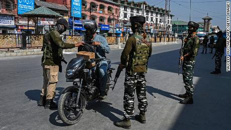 Security personnel check the bag of a motorist on the side of a road in Srinagar on October 9.