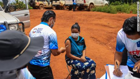 A woman receives a dose of the Pfizer vaccine on October 5, 2021 in the district of Gua Musang, Kelantan, Malaysia.