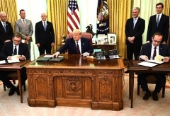 President Trump watches as Kosovar Prime Minister Avdullah Hoti, right, and Serbian President Aleksandar Vucic sign an agreement on normalizing economic relations, in the Oval Office on Friday. (Photo by Brendan Smialowski/AFP via Getty Images)