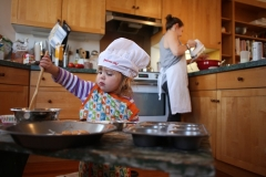 A toddler gets helps mom bake. (Photo by Tim Clayton/Corbis via Getty Images)