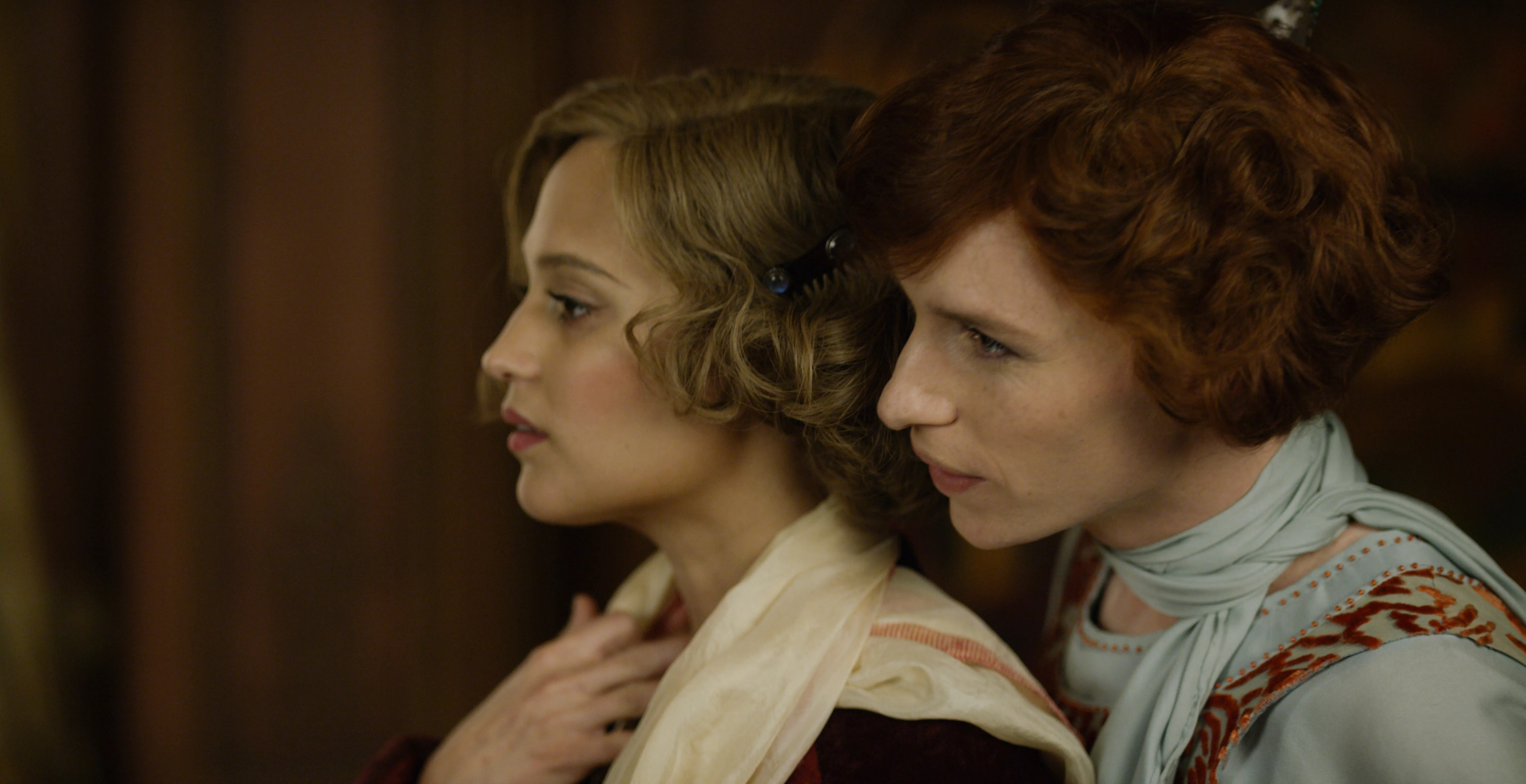 Still from The Danish Girl (2015). A close up of Gerda and Lili in profile. Gerda is facing away from Lili, who stands close behind her, looking over her shoulder in a tender moment.