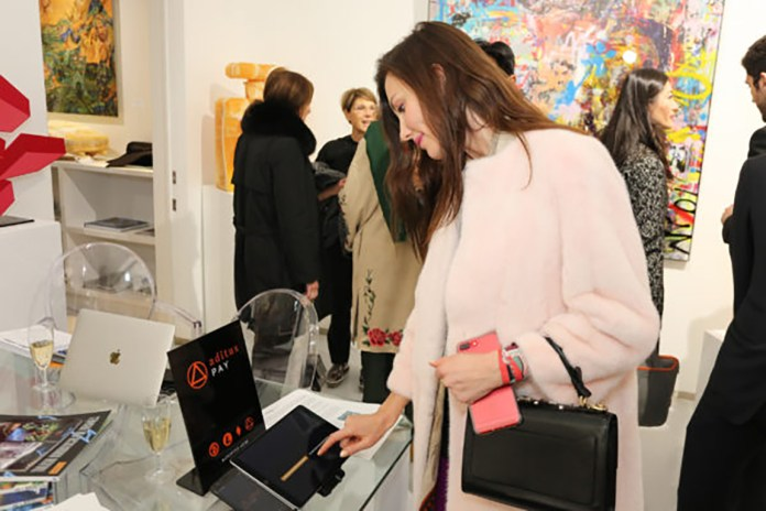 A guest trying out the Aditus Pay cryptocurrency payment gateway at the Bel-Air Fine Art Gallery at its grand opening in London, United Kingdom.