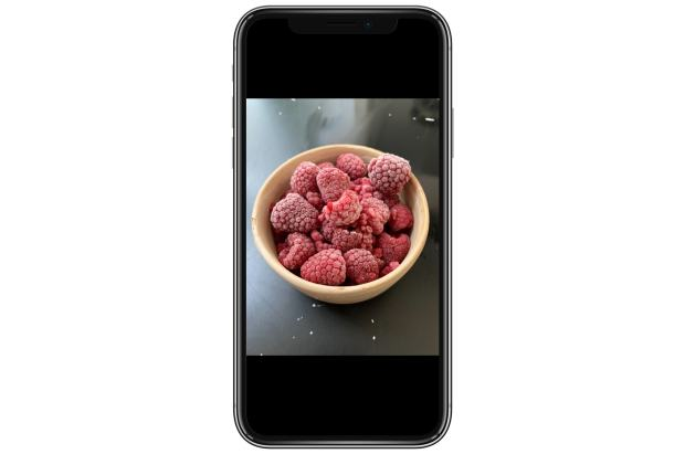 A phone with a bowl of raspberries