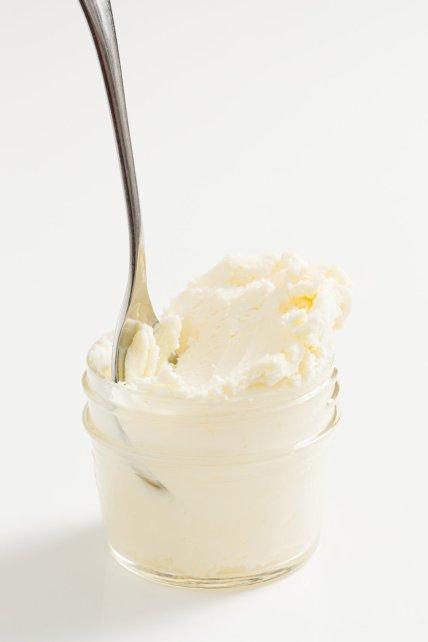 Un frasco de crema coagulada con una cuchara descansando dentro