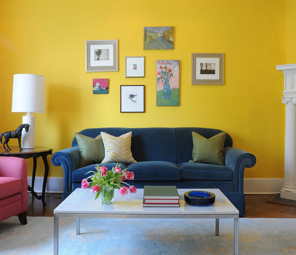 Color Theory Paint the Walls Bright Yellow Walled Living Room with Soft Toned Furniture Rose Accent Chair White Table Lamp Coffee Table Flowers Gallery Wall