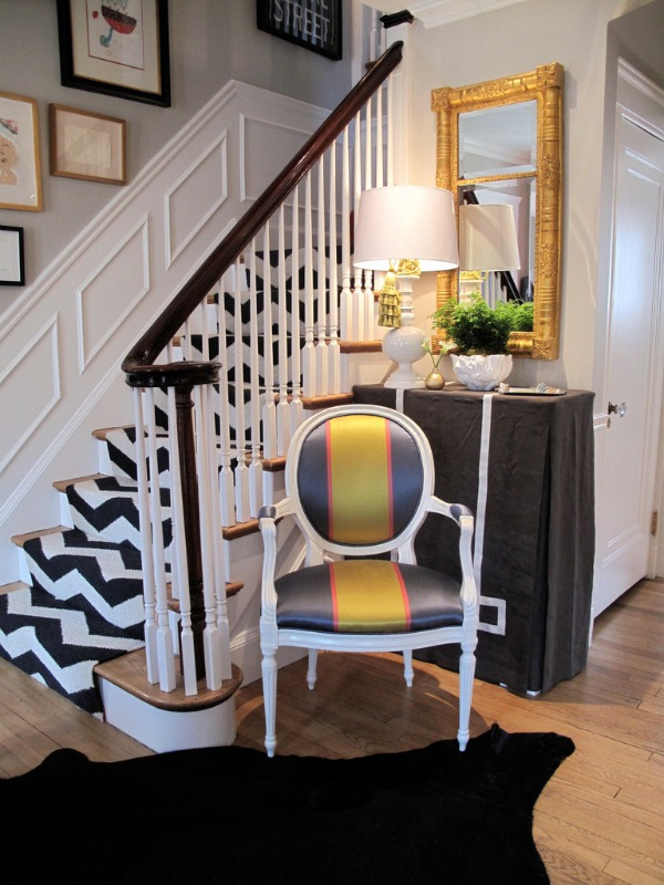 Textiles and Textures Entryway Interior Design with Patterned Stairway in Black and White Chevron with Yellow and Gray Chair and Black Rug