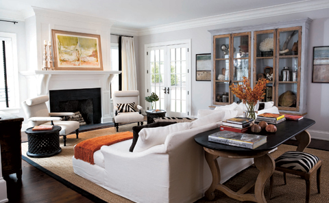 Elle Decor - living rooms - glass front cabinet, zebra bench, sofa table, wood sofa table,  Skye Kirby - Crisp, clean white & orange family room!