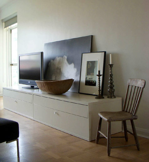 living rooms - TV white media console cabinet parquet wood floors  The placement of art and accessories makes the TV part of an arrangement.