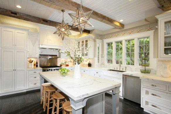 kitchens - Moravian Star Pendant white beadboard ceiling rustic exposed wood beams white kitchen cabinets calcutta gold marble countertops gray kitchen island gray walls starfish decor stools