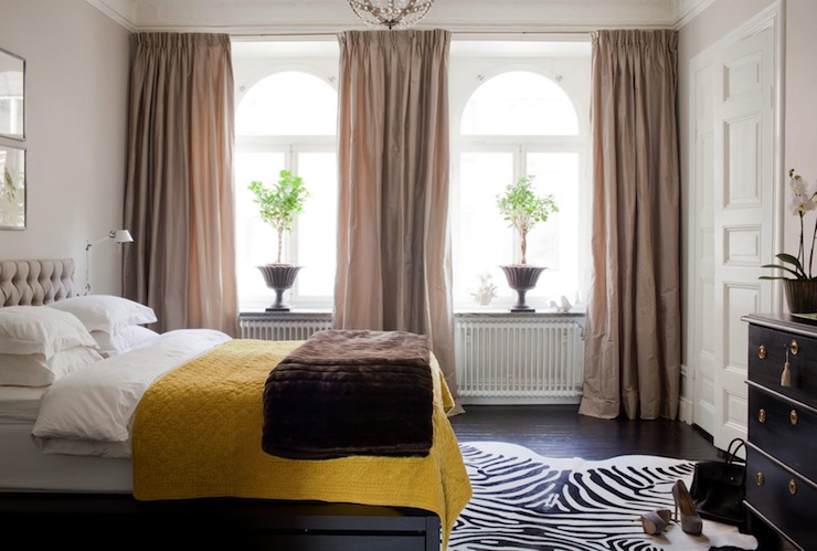 bedrooms - taupe silk organze drapes gray tufted headboard chocolate brown faux fur throw layered yellow blanket zebra cowhide rug black chest