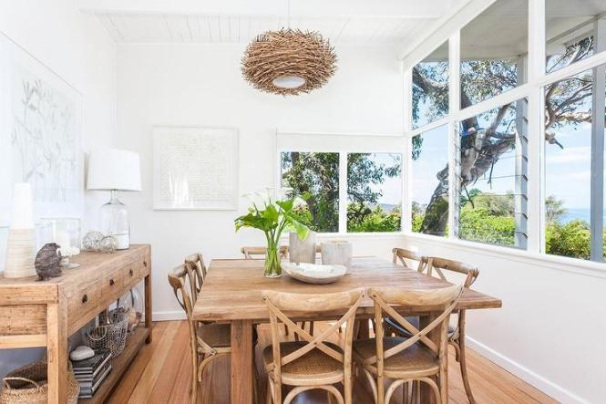 Coastal Style Dining Room Boasts A Bird S Nest Chandelier Hanging Over Square Salvaged Wood Table Lined With Eight X Back Chairs Situated