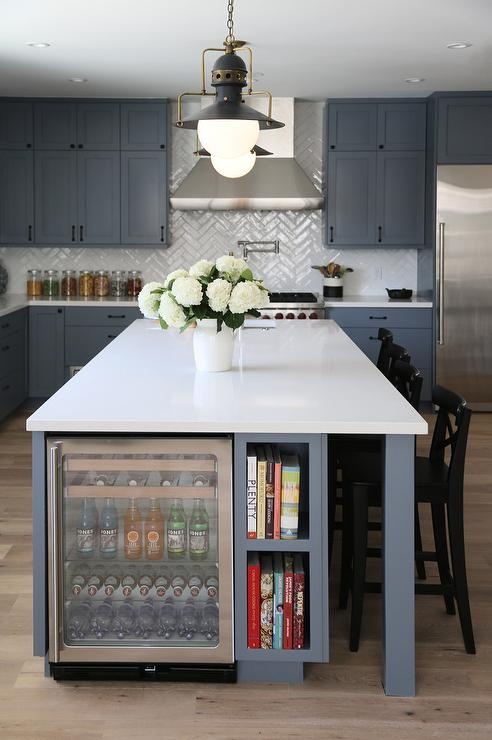 We may earn commission on some of the items you choose to buy. Steel Gray KItchen Island with Glass Beverage Fridge Next to Cookbook Shelves - Contemporary