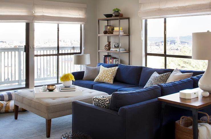 Blue Sectional With Light Gray Tufted Ottoman As Coffee