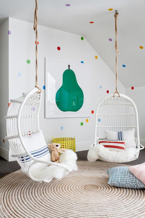 girls room with white hanging chairs