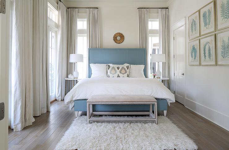 Blue Upholstered Bed With Small Gold Sunburst Mirror