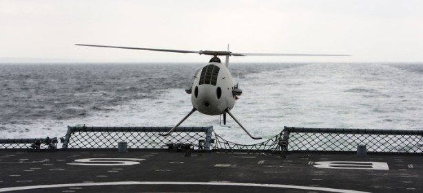 A Schiebel Camcopter S-100 drone hovers during a test aboard a ship.