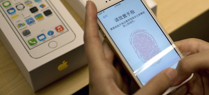 In this Sept. 20, 2013 file photo, a customer configures the fingerprint scanner technology built into the Apple iPhone 5S at an Apple store in Wangfujing shopping district in Beijing.