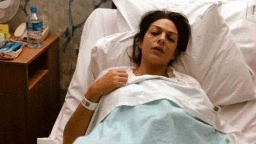 Nicole aparecia deitada em uma cama de hospital, com expressão de dor