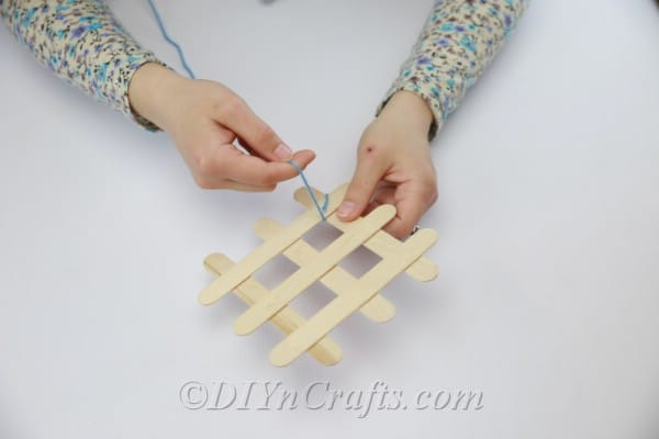 Wrap yarn in corners where popsicle sticks meet