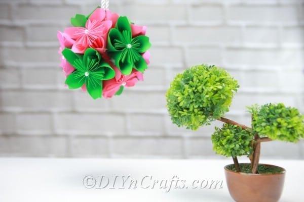 Paper flower ball hanging above a small plant