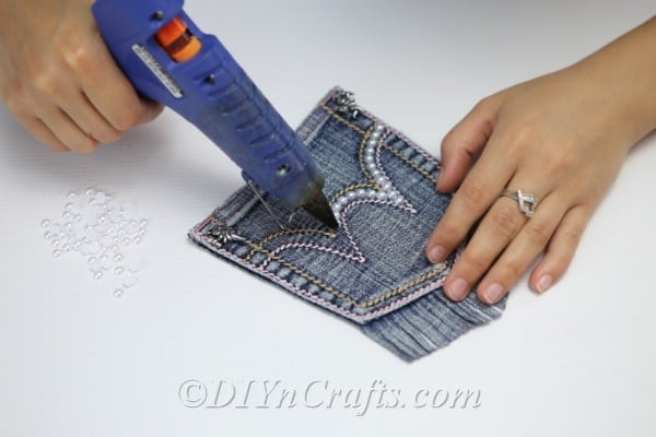 Gluing fake pearls along seams on pocket denim bag