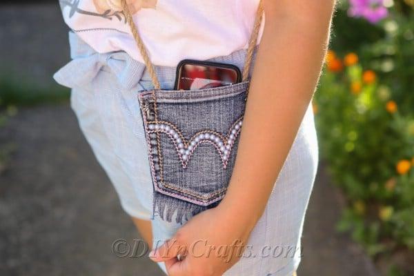 Cute denim pocket bag filled with a smartphone.