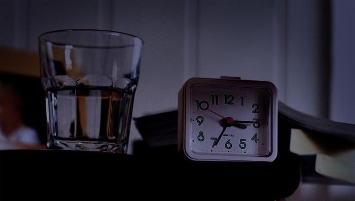 bicchiere d'acqua accanto alla notte del letto