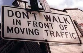 "Street sign that reads, ""Don't walk in front of moving traffic"""