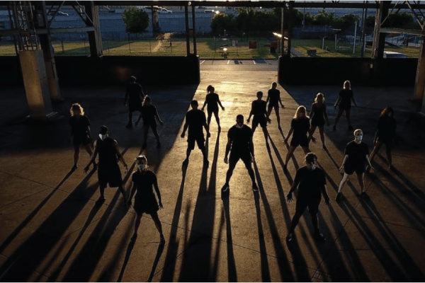 A photo of a group of backlit dancers