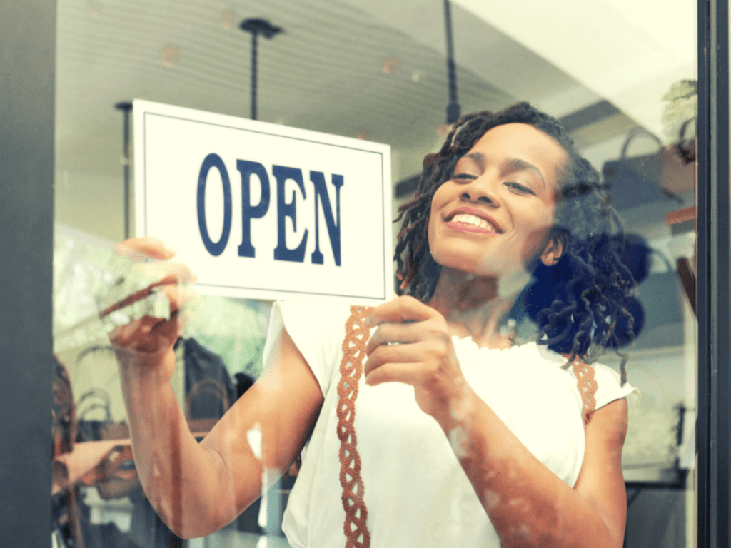 """A woman in a storefront turns around an """"open"""" sign."""
