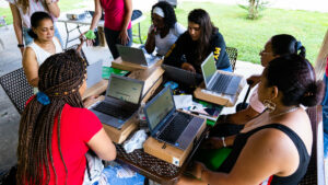Six women sit around a table in an outdoor pavilion looking at laptops. They are participating in a Tech Goes Home course with Bridge Refugee Services.